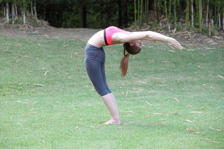 chandrasana: Yoga Ardha Chandrasana (back bend) pose by woman on lawn