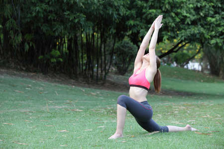 Woman practicing Warrior yoga pose outdoors on lawn
