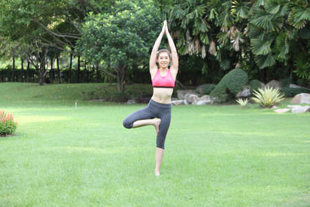 Young woman practicing tree yoga pose on lawn,left side photo