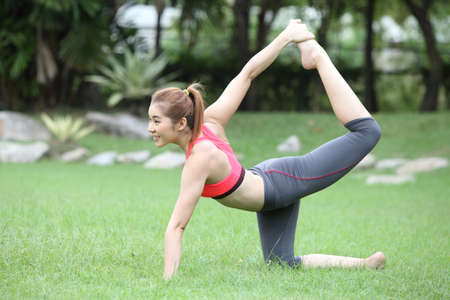 Sporty yoga girl doing exercises for buttocks on lawn Stock Photo