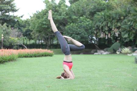 headstand: Young Woman in Headstand Yoga Pose on lawn