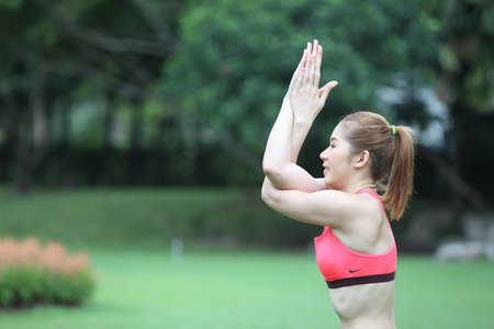 pointed arm: Half portrait Young Woman in engle arms Yoga Pose on lawn Stock Photo