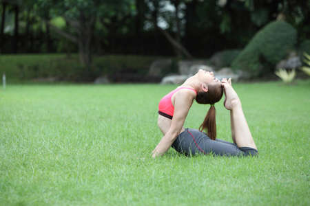 pada: Young woman practicing yoga, eka pada Rajakapotasana (King Pigeon Pose) pose on lawn
