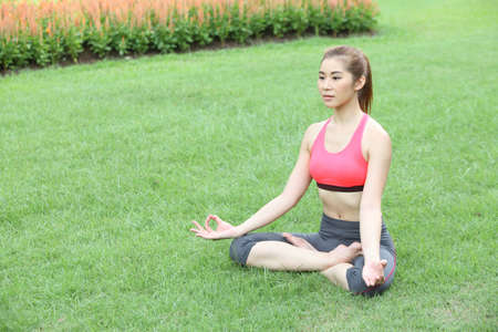 Young girl doing yoga in lotus pose in the lawn Stock Photo