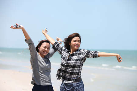 invigorate: Two woman feel happy on the beach