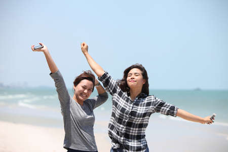 invigorate: Two woman feel happy on the beac