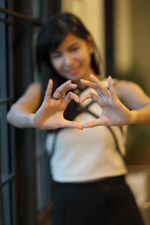 handsign: cute woman show couple hand in heart shape