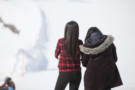 Two women looking at view of snow resort