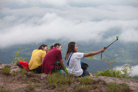 Loei ,THAILAND - October 2, 2017 :Women Traveler take photo her and his friends by action camera at view point on Phukardueng peak