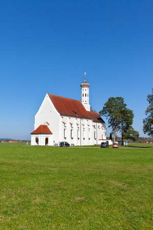 Church sits alone among a field over blusky