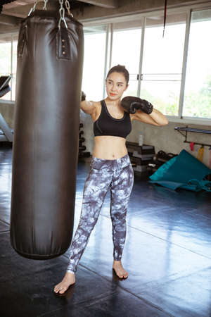 Young beautiful woman punching A Bag With Boxing Gloves On