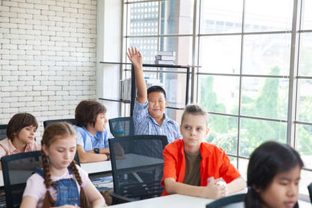 group of school kids clapping hands in classroom (education concept)