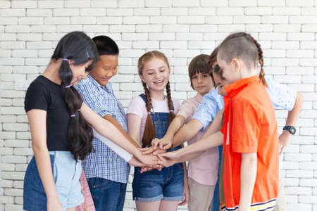 Group of kids holding their hands together on blurred background, closeup