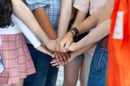 Group of people holding their hands together on blurred background, closeup