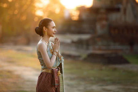 Thai young woman in thai traditional dress are paying respect , Thai Girl Sawasdee