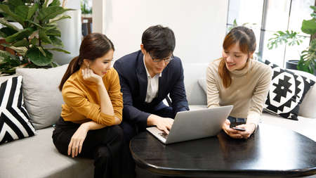 Smiling  employees sit and talk at office desk look at laptop screen cooperating in office Stockfoto