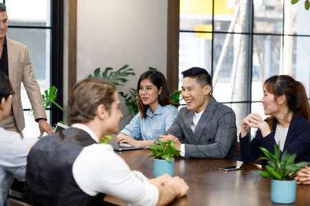 Group of contemporary businesspeople working in meeting focus on man laughing happily