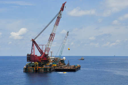 crane barge lifting heavy cargo or heavy lift in offshore oil and gas industry. Large  boat working for lift piping and installation the platform. Banco de Imagens