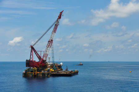 boat lift: crane barge lifting heavy cargo or heavy lift in offshore oil and gas industry. Large  boat working for lift piping and installation the platform. Stock Photo
