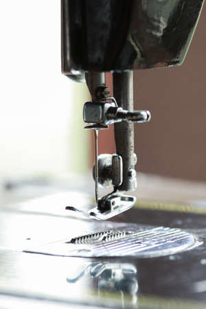 sewing item: the sewing machine and item of clothing, Detail of sewing machine and sewing accessories, old sewing machine. Stock Photo