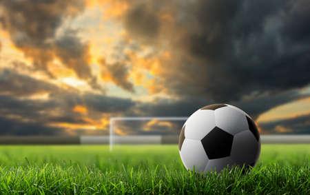 夕日を背景に緑の芝生の上のサッカー ボール。
