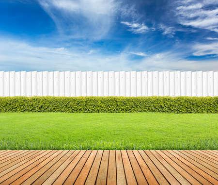 Gazon en houten vloer met haag en witte hek op blauwe hemel achtergrond