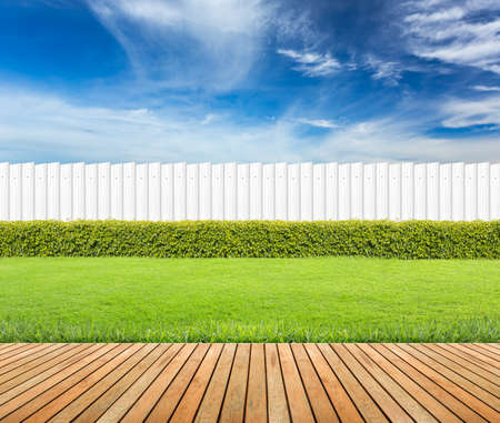 Lawn and wooden floor with hedge and White fence on blue sky background Archivio Fotografico