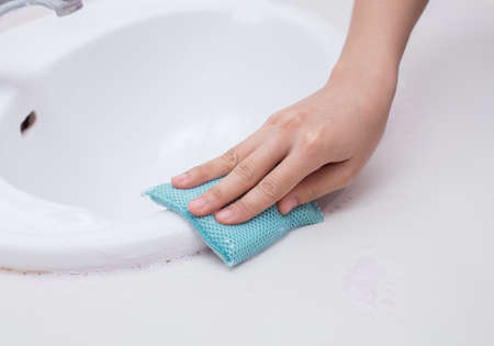 Hand with sponge cleaning white sink and faucet photo