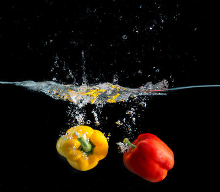fruit in water: yellow and red pepper falling and splashing into water.