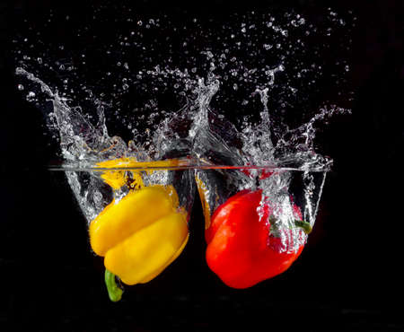 yellow and red pepper falling and splashing into water.