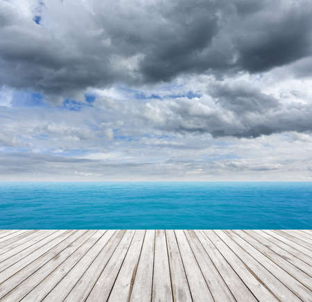 Wooden Floor under cloudy sky with sea photo