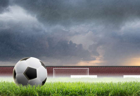 Soccer ball on field with rain background