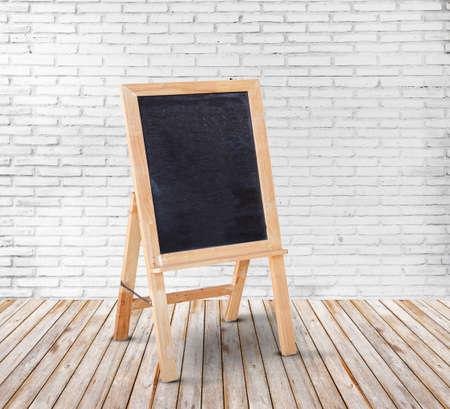 Blank blackboard on wood floor and white brick wall background