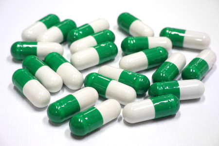 green and white capsules on white background photo