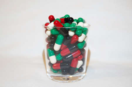 rouge et noir: Red black and green white capsules in a little glass