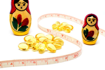 babushka: Russian Babushka nesting dolls and Omega 3 capsules with measuring tape for dieting concept