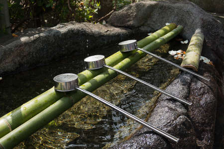 purification: Japanese purification water and stainless ladles at entrance of the Japanese temple