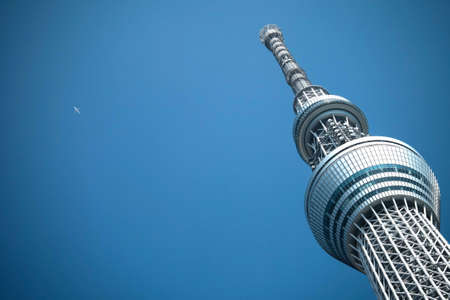 tele up: Tokyo, Japan - Mar 22, 2016 : Tokyo Sky Tree tower with the aeroplane from the far of clear sky, Tokyo Skytree is the tallest structure in Japan in 2010.
