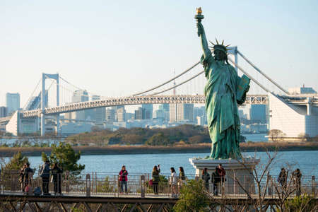 elevated walkway: Tokyo, Japan - Mar 22, 2016 : Unidentified people at an elevated walkway in Odaiba visiting the view of  The Statue of Liberty and the Rainbow Bridge.