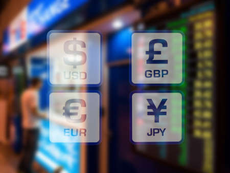 currency icons on currency exchange booth at airport blurred background Stock Photo