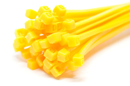 zip tie: Cable tie in yellow isolated on white background Closeup Stock Photo