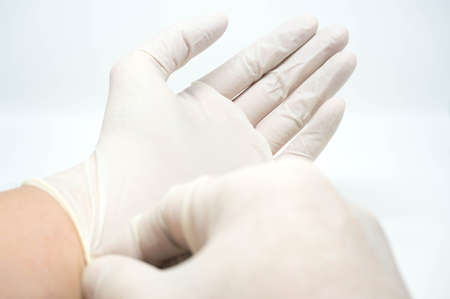 surgical: poniendo en guantes blancos desechables estériles sobre fondo blanco