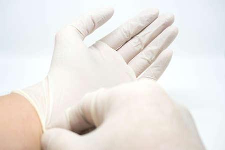 uvedení na jedno použití sterilních bílých rukavicích na bílém pozadí Reklamní fotografie