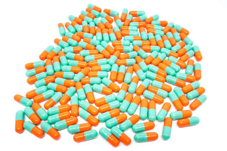 green orange color pills capsule on white background