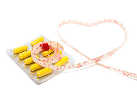 purgative: herb pills blister pack and measuring tape heart shape for diet concept