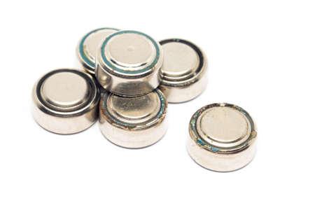 kleine horloge roestige batterijen op een witte achtergrond