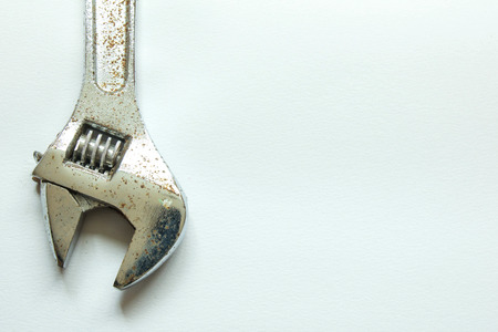 crescent wrench: Rusty adjustable wrench in white background