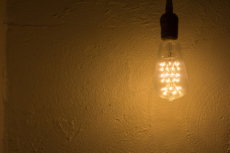 iluminate: Lightbulb hang on white concrete wall