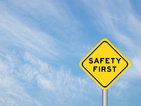 road work: wording Safety first on yellow traffic sign on the blue sky Stock Photo
