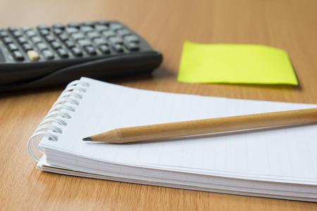 cuadro sinoptico: Nota de papel, calculadora y l�piz sobre la mesa de madera